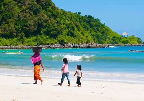 Indonesian Family Walking Along Selong Belanak Beach, South Lombok, Indonesia. Selong Belanak is definitely in the top 5 beaches I have been to. The sea is unbelievably clear and the sand, impossibly white. With only one small beach hut selling local Indonesian food and no public transport to the beach, Selong Belanak beach is unsuprisingly completely deserted and is a great example of a traditional, unspoilt Lombok fishing village.
